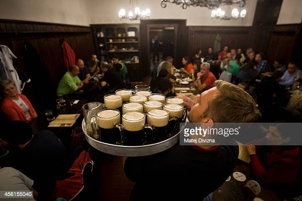A waiter distributes glasses of dark beer to customers at the famed U Fleku pub on the eve of the Czech Beer Day on September 26 2014 in Prague Czech...