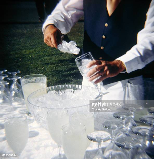 Waiter Filling Glass with Ice Cubes