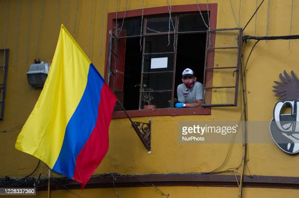 A waiter form a restaurant sees from the window alongside Colombian Flag the at el Chorro de Quevedo as part of the pilot to re open restaurants...