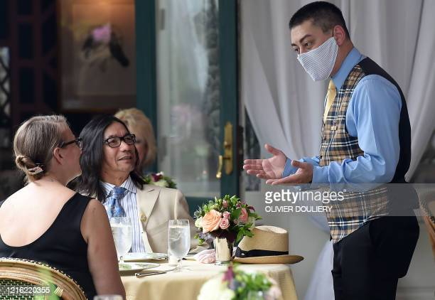 A waiter from The Inn at Little Washington one of the countrys most renowned restaurants wears a face mask while talking to customers on the first...
