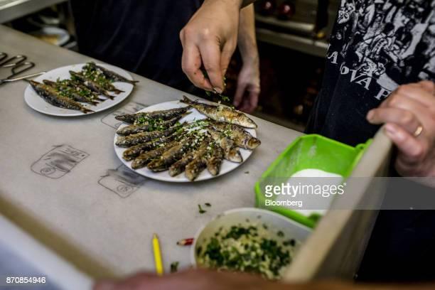 Waiter garnishes plates of sardines at the Cova Fumada restaurant in the Barceloneta neighborhood in Barcelona, Spain, on Saturday, Nov. 4, 2017....