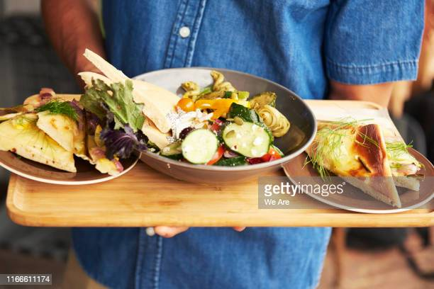 waiter holding a platter of vegetarian food - vegetarianism stock pictures, royalty-free photos & images