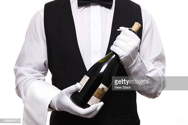 Waiter holding bottle of red wine