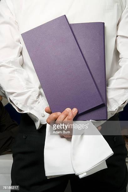 A waiter holding menus behind his back