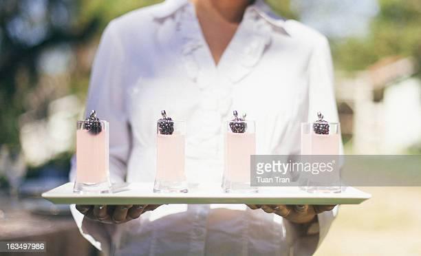 Waiter holding multiple glasses at wedding