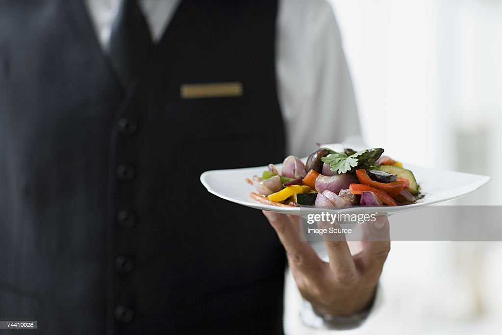 Waiter holding plate : Stock Photo