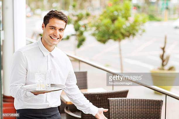 Waiter Holding Serving Tray With Drinks Welcoming In Restaurant