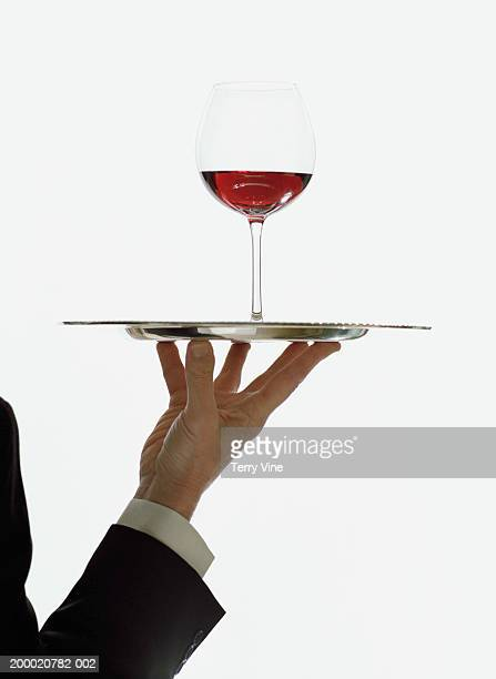 Waiter holding silver tray with wine glass