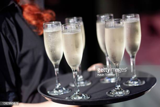 waiter holding tray full of champagne glasses - ereignis atmosphäre stock-fotos und bilder