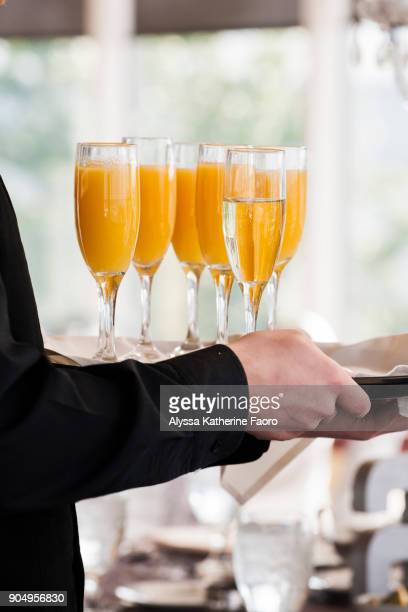 waiter holding tray of champagne and mimosas - mimosa stock pictures, royalty-free photos & images