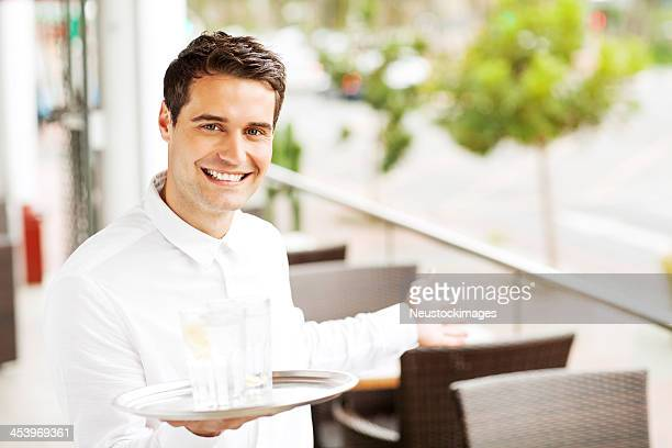 Waiter Holding Tray While Welcoming In Restaurant