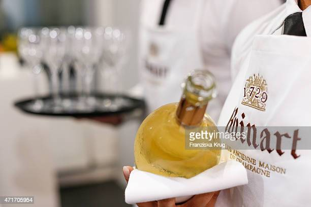 A waiter holds a bottle of Ruinart Champagne during the Hubert le Gall Vernissage At Ruinart PopUp Gallery on April 30 2015 in Berlin Germany