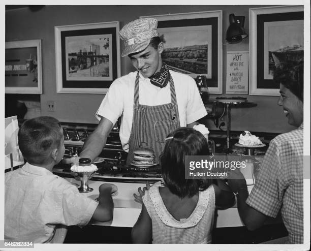 A waiter in a train engineer's costume smiles at children as the restaurant's gimmick a model train that serves the food pulls in loaded with the...