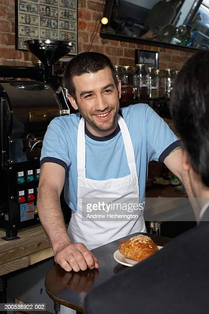 Waiter in cafe smiling at customer