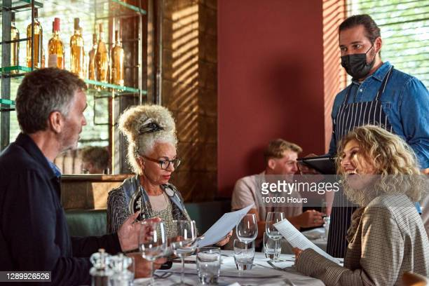 waiter in face mask serving customers - essential services stock pictures, royalty-free photos & images