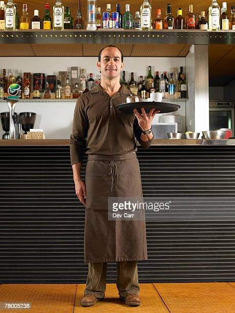 Waiter in long apron holding tray in front of bar.