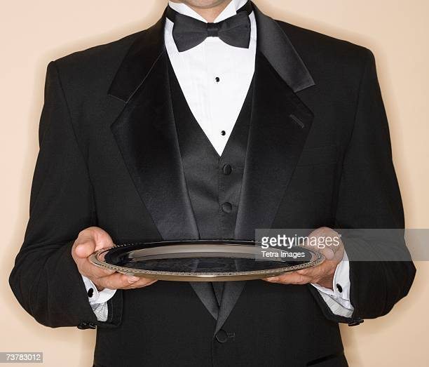 waiter in tuxedo holding silver platter - serving tray stock pictures, royalty-free photos & images