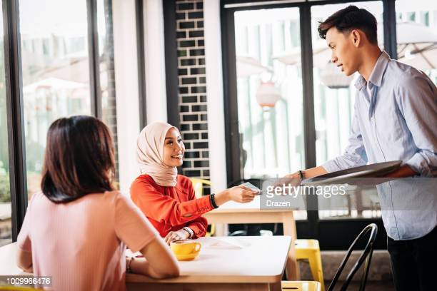 Waiter is bringing receipt to customers in nice cafe in Asia