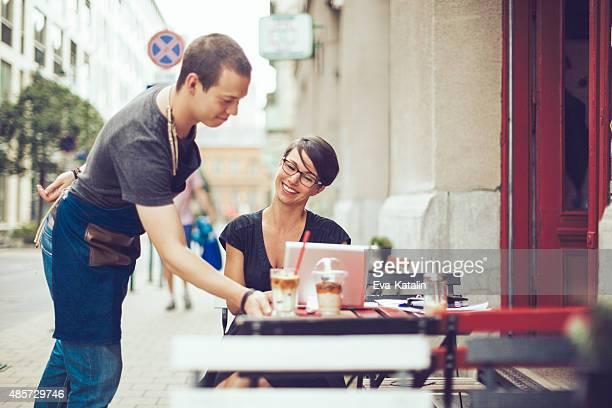 Camarero sirve un café para un cliente.