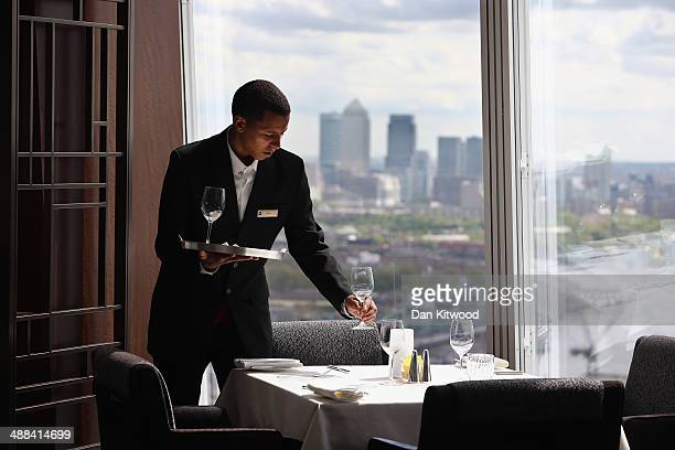 A waiter lays a table ahead of a reception on the 35th floor of the ShangriLa Hotel at the Shard on May 6 2014 in London England The Shangri La Hotel...