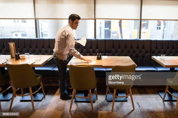 A waiter lays a table for lunch in a Bar and Block restaurant operated by Whitbread Plc in London UK on Wednesday Jan 17 2018 The hotel and...
