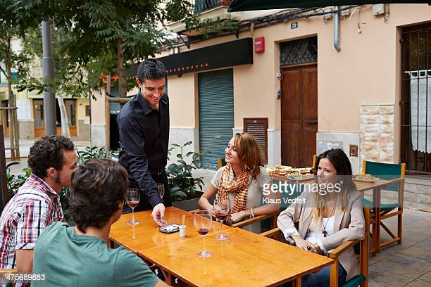 waiter leaving the bill at table with 4 guests - klaus vedfelt mallorca stock pictures, royalty-free photos & images