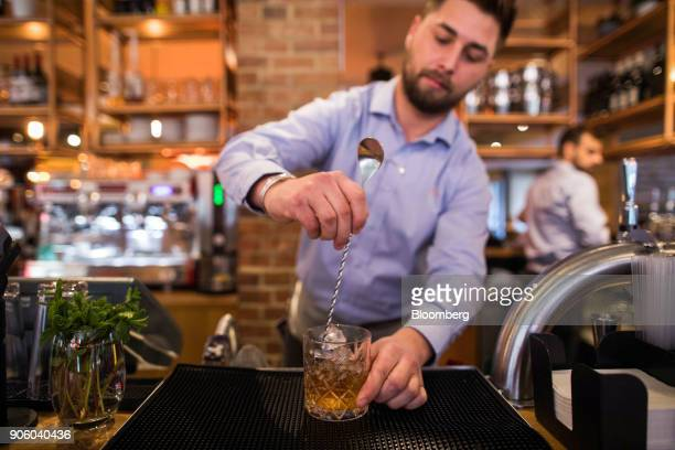 A waiter mixes ice in to a cocktail in a Bar and Block restaurant operated by Whitbread Plc in London UK on Wednesday Jan 17 2018 The hotel and...