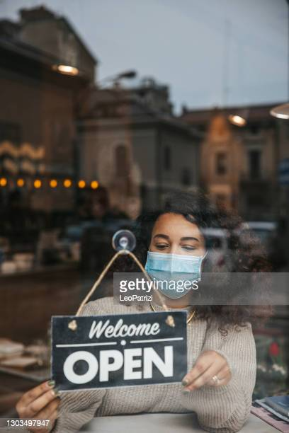 waiter of a restaurant attaching the open sign on the window - store opening stock pictures, royalty-free photos & images