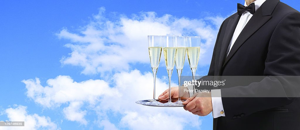 Waiter offering champagne at open air party : Stock Photo