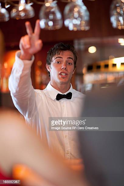 Waiter offering more drinks at bar