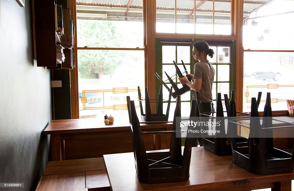 Waiter packing up cafe or restaurant chairs : Stock Photo