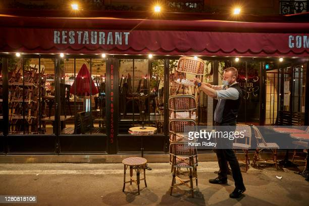 Waiter packs up a bar before a city wide curfew comes into effect in Paris on October 17, 2020 in Paris, France. The nightly curfew, announced by...