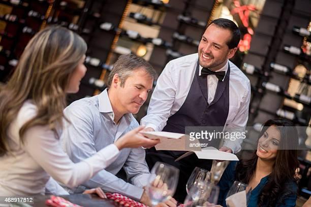 Waiter passing menus to customers at a restaurant