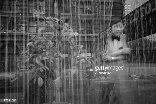 A waiter peers from the window of the 'Lotus Eaters Fifth' Chinese restaurant Upper East Side New York City 1981