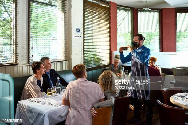 waiter photographing family in restaurant - social gathering stock pictures, royalty-free photos & images
