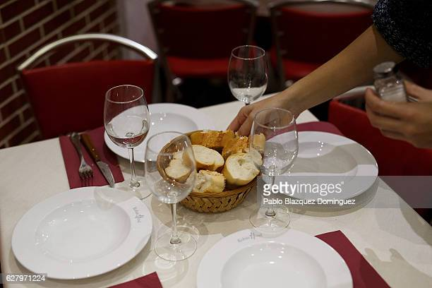 A waiter places bread on a table before homeless people enter to have free dinner at Robin Hood restaurant on December 5 2016 in Madrid Spain...