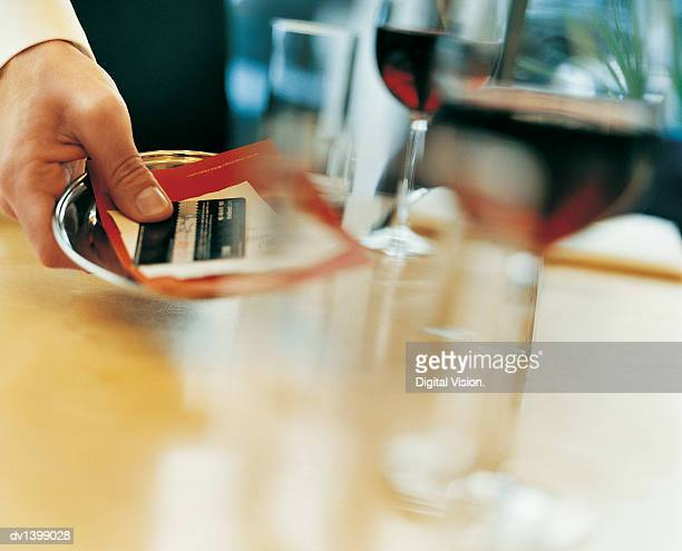 Waiter Placing a Bill and a Bank Card on a Table in a Restaurant