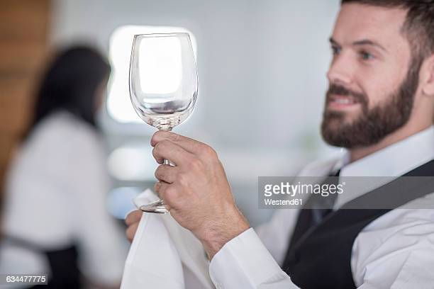 Waiter polishing wine glasses in restaurant
