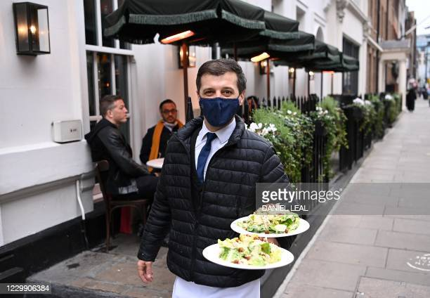 Waiter poses for a photograph as he carries a customer's order to their table outside a restaurant in London on December 2, 2020 as England emerges...