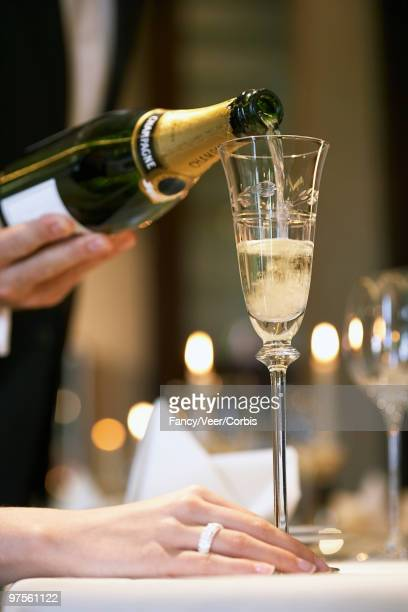 Waiter pouring champagne into woman's glass