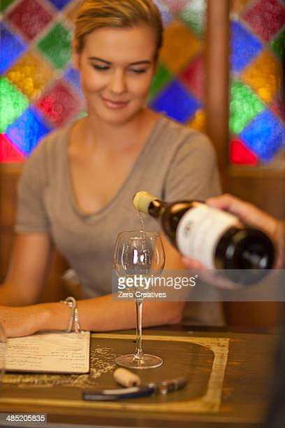 Waiter pouring glass of white wine for a young woman