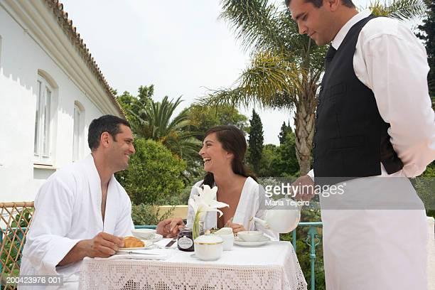 Waiter pouring tea for couple having breakfast on terrace, smiling