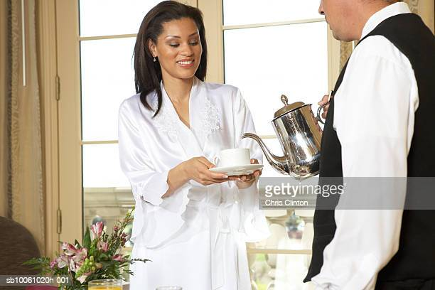 Waiter pouring tea for mid adult woman in hotel room