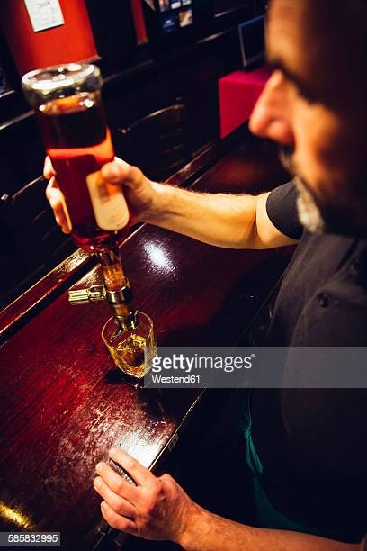 Waiter pouring whiskey in an Irish pub