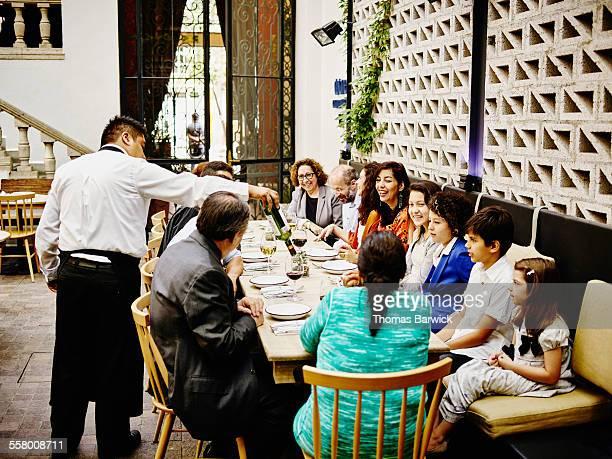 Waiter pouring wine for family in restaurant