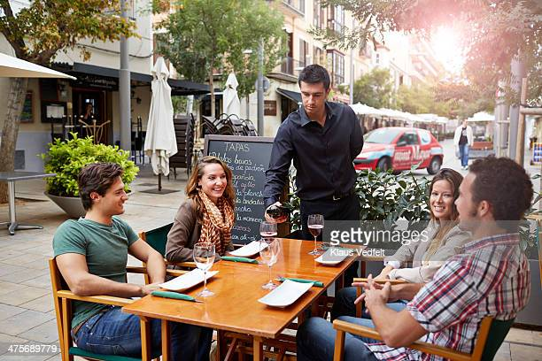 waiter pouring wine for guests at restaurant - klaus vedfelt mallorca stock pictures, royalty-free photos & images