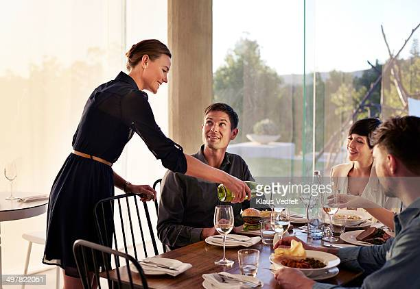 Waiter pouring wine for guests