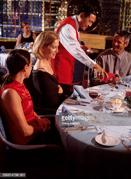 Waiter pouring wine into glass for people sitting at table in restaurant