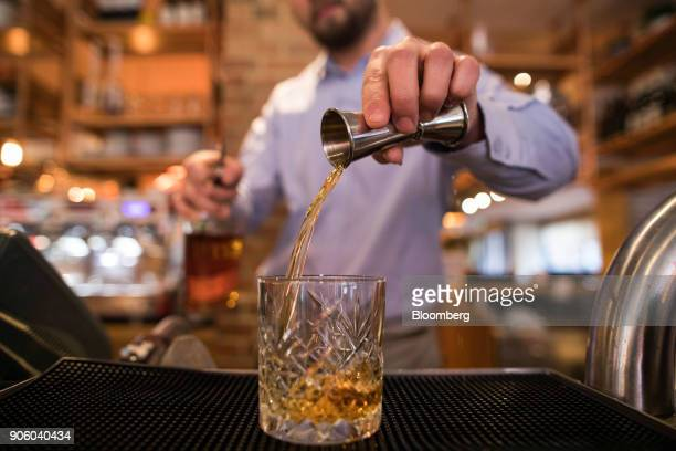 A waiter pours a bourbon whisky into a glass in a Bar and Block restaurant operated by Whitbread Plc in London UK on Wednesday Jan 17 2018 The hotel...