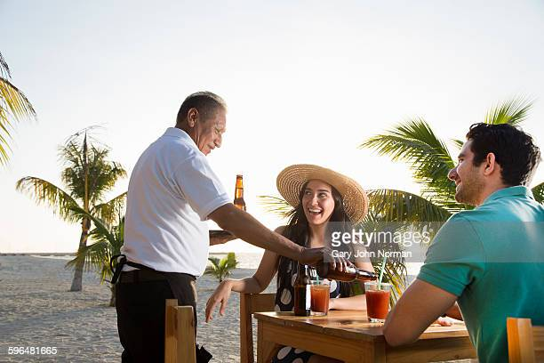 waiter pours a drink for couple at table on beach - serving food and drinks stock pictures, royalty-free photos & images